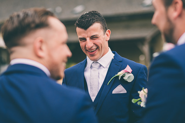 Groom laughing at Great Tythe Barn