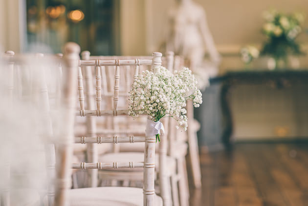 Flowers on chairs during ceremony