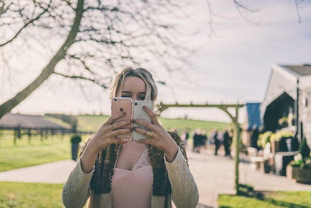 Girl holding two iPhones at Wedding
