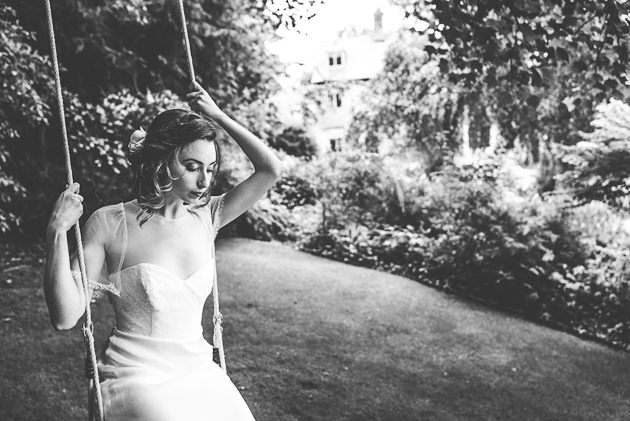 Bride swinging on rope swing in black and white