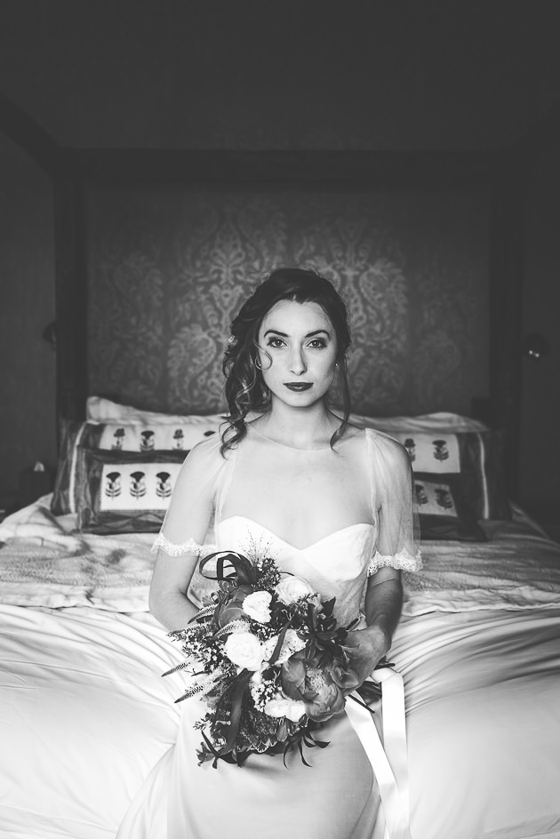 Bride sat on bed looking at camera