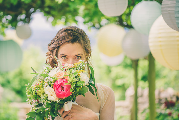 Bride holding bouquet towards face