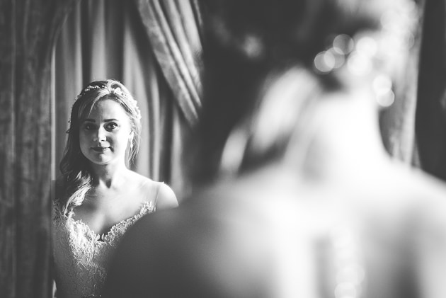 Bride looking in long mirror